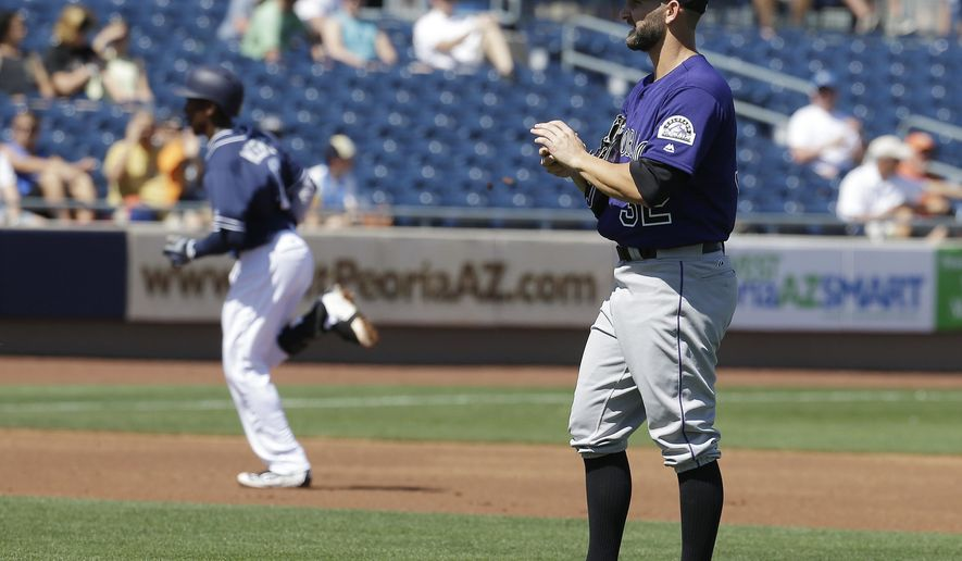 Colorado Rockies' Tyler Chatwood, right, gets a new baseball after giving up a two-run home run to San Diego Padres' Jemile Weeks during the first inning of a spring training baseball game on Saturday, March 19, 2016, in Peoria, Ariz. (AP Photo/Darron Cummings)