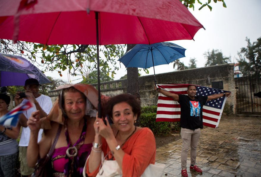 A handful of Cubans gather under a steady rain to wave to President Obama's convoy as it arrives in Old Havana in Cuba on Sunday. Seeing few opportunities in Cuba, most of the young people on the island of 11 million say they want to leave. (Associated Press)
