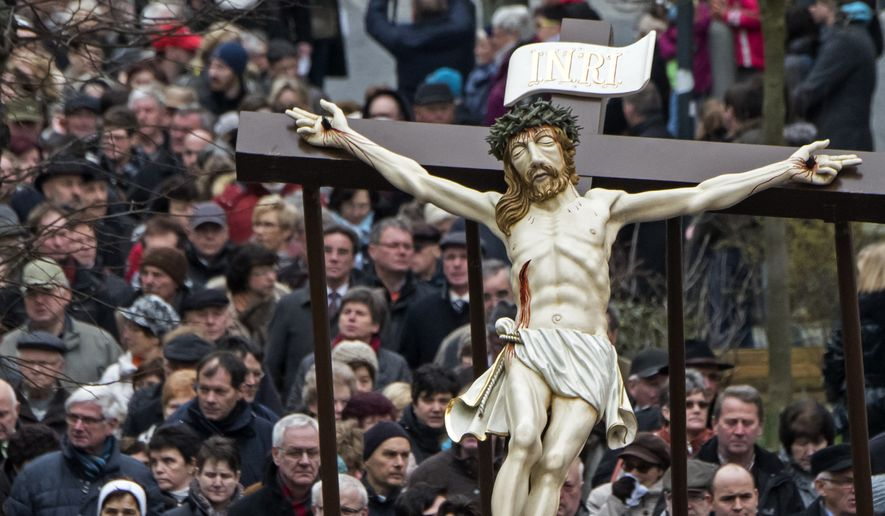 People carry the cross of the scene 'Crucifixion' at the Palm Sunday Procession in the old town in Heiligenstadt, Germany, Sunday, March 20, 2016.  Thousands of believers from the region and all over Germany attend the procession when participants carry life-size figures showing the Passion of Christ.(AP Photo/Jens Meyer)