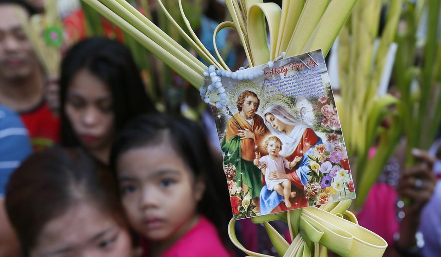 Roman Catholic devotees carry palm fronds to be blessed by a priest as they commemorate Palm Sunday which marks the beginning of Holy Week Sunday, March 20, 2016 at the Redemptorist Church in Baclaran, south of Manila, Philippines. Palm Sunday, which is the final week of Lent, marks the triumphant entry of Jesus Christ into Jerusalem. The palm fronds end up in homes of devotees for a year, to be burned after and its ashes to be used for Ash Wednesday for next Season of Lent. (AP Photo/Bullit Marquez)