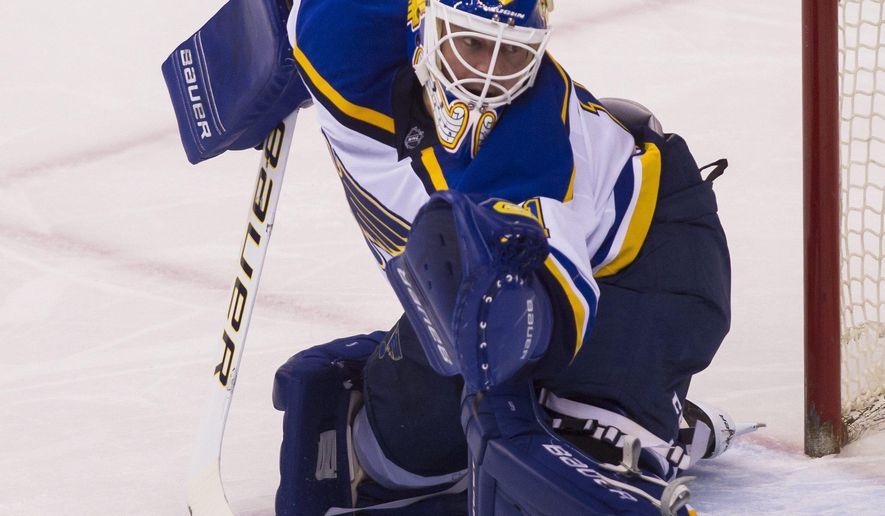 St. Louis Blues goalie Brian Elliott makes a save against the Vancouver Canucks during the second period of an NHL hockey game Saturday, March 19, 2016, in Vancouver, British Columbia. (Ben Nelms/The Canadian Press via AP)