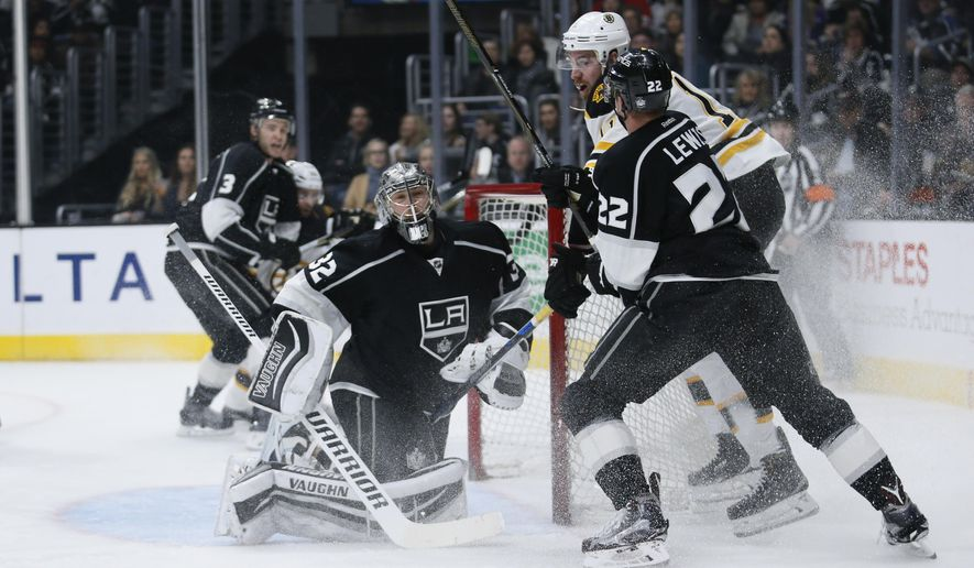 Los Angeles Kings goalie Jonathan Quick, left, protects the net while Kings' Trevor Lewis, right, pushes Boston Bruins right wing Jimmy Hayes, right, away during the first period of an NHL hockey game, Saturday, March 19, 2016, in Los Angeles. (AP Photo/Danny Moloshok)
