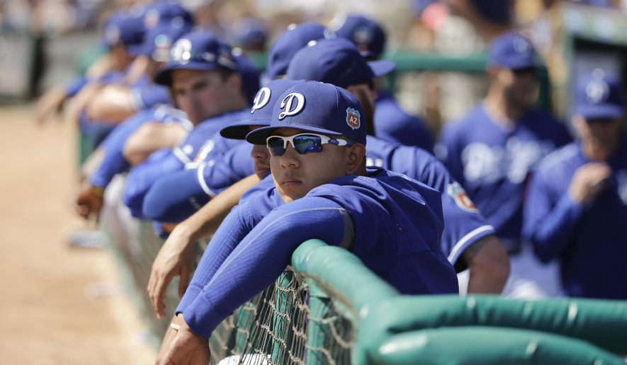 In this photo taken Monday, March 14, 2016, Los Angeles Dodgers starting pitcher Julio Urias, center, watches from the dugout during the team's spring training baseball game against the Milwaukee Brewers in Phoenix. Spanish-speaking players from Latin America usually struggle with a new language. MLB instructed its 30 teams this season to hire full-time Spanish interpreters for their Latin players. (AP Photo/Jae C. Hong)