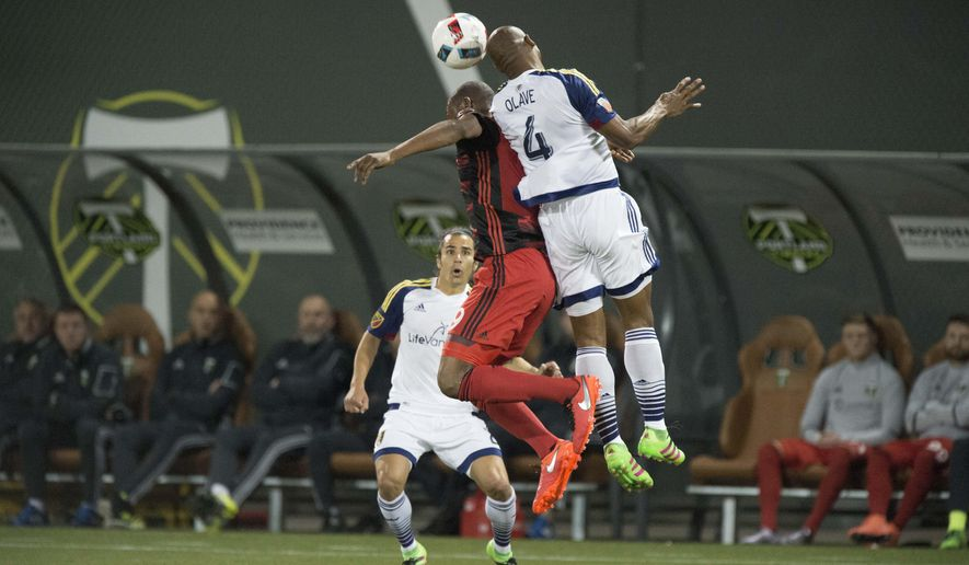 Portland Timbers forward Fanendo Adi (9) battles for a header against Real Salt Lake defender Jamison Olave (4) during the first half of an MLS soccer game at Providence Park in Portland, Ore., Saturday, March 19, 2016. (AP Photo/Troy Wayrynen)