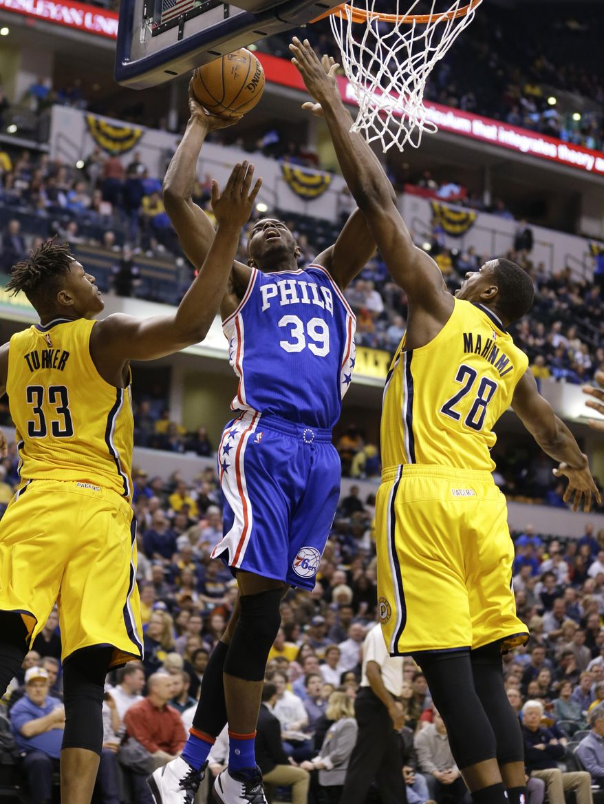 Philadelphia 76ers forward Jerami Grant (39) shoots between Indiana Pacers forward Myles Turner (33) and center Ian Mahinmi (28) during the first half of an NBA basketball game in Indianapolis, Monday, March 21, 2016. (AP Photo/Michael Conroy)