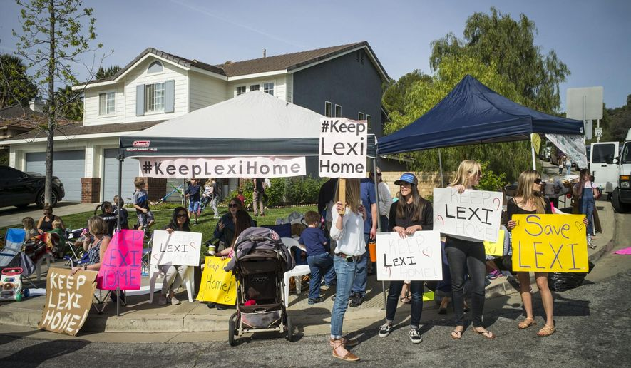 Supporters of Lexi's foster family hold a rally for the family outside Lexi's foster home in Santa Clarita, Calif., Monday, March 21, 2016. Lexi, who spent most of her life with California foster parents, was removed from her home on Monday under a court order that concluded her native American blood requires her placement with relatives in Utah. (David Crane/Los Angeles Daily News via AP) MANDATORY CREDIT