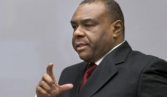 Jean-Pierre Bemba enters the court room of the International Criminal Court in The Hague, Netherlands, Monday, March 21, 2016. The International Criminal Court is passing judgment on former Congolese vice president Bemba on charges of commanding a militia that went on a spree of murder, rape and pillage in Central African Republic more than a decade ago. The verdicts being delivered Monday afternoon focus on the responsibility of a military commander for the actions of his troops. Bemba's long-running trial also was the first at the ICC to feature allegations of systematic sexual abuse by soldiers in a conflict. (AP Photo/Jerry Lampen, Pool)