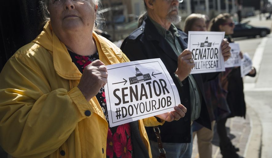 Libby Earle, of Hamilton, left, and others, picket outside the office of Sen. Rob Portman, R-Ohio, Monday, March 21, 2016, in Cincinnati. A coalition of liberal groups staged rallies around the country on Monday targeting Republican senators who oppose confirmation hearings for President Barack Obama's Supreme Court nominee Merrick Garland. Portman has stood firm with other Republicans in arguing that the next president should fill the court vacancy after American voters weigh in this November. (AP Photo/John Minchillo)