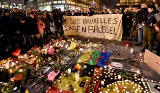 mourning: A crowd gathers at Place de la Bourse in the center of Brussels to hold a candlelight vigil for victims of the Tuesday bombings at the Zaventem Airport and one of the city's metro stations, where scores were killed and wounded. (Associated Press photographs)
