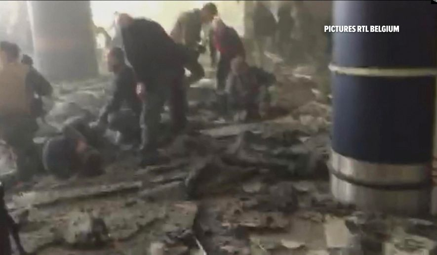 In this still image taken from video from RTL Belgium  people receive treatment in the debris strewn terminal at Brussels Airport, in Brussels after explosions Tuesday, March 22, 2016.  (RTL via AP)