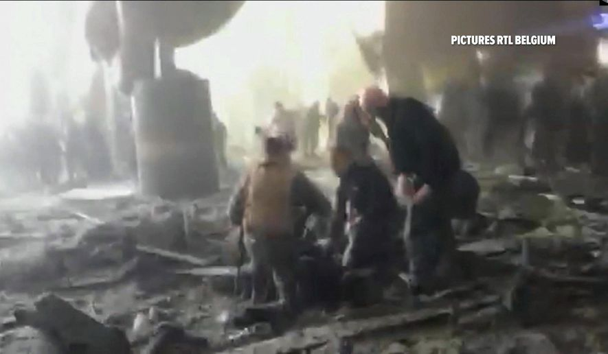 In this still image taken from video from RTL Belgium  people receive treatment in the debris strewn terminal at Brussels Airport, in Brussels after explosions Tuesday, March 22, 2016. Authorities locked down the Belgian capital on Tuesday after explosions rocked the Brussels airport and subway system, killing  a number of people and injuring many more. Belgium raised its terror alert to its highest level, diverting arriving planes and trains and ordering people to stay where they were. Airports across Europe tightened security.  (RTL via AP) BELGIUM OUT TV OUT NO ARCHIVE