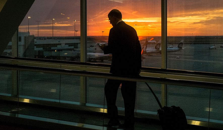 A traveler looks at his smartphone as he rides the moving sidewalk at Denver International Airport. (Associated Press)