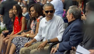 President Barack Obama, with members of the first family, talks with Cuban President Raul Castro as they attend an exhibition baseball game between the Tampa Bay Rays and the Cuban National team at the Estadio Latinoamericano, Tuesday, March 22, 2016, in Havana, Cuba. (AP Photo/Pablo Martinez Monsivais)