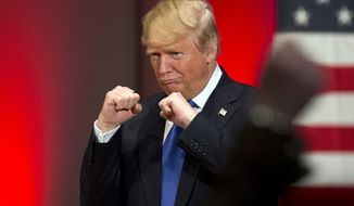In this Jan. 28, 2016, photo, Republican presidential candidate Donald Trump poses with a ring given to him by a group of veterans during a campaign event on the campus of Drake University in Des Moines, Iowa. For some Americans, the promise of political change and disruption has come too slowly, or failed altogether. On the eve of the first voting contest in the 2016 presidential election, these voters are pushing for bolder, more uncompromising action, with an intensity that has shaken both the Republican and Democratic establishment. (AP Photo/Jae C. Hong)