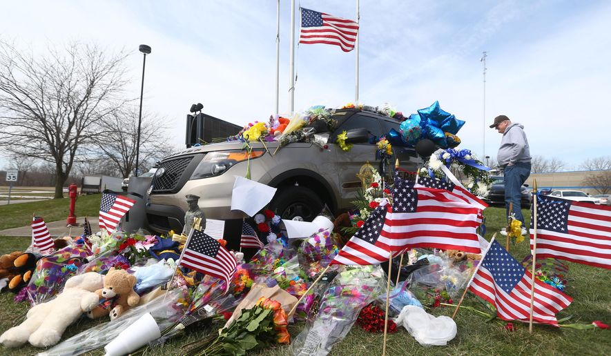 Retired Howard County Sheriff Deputy Jon Zeck admires the outpouring community support of flowers, stuffed animals, American flags, and messages that decorate Deputy Carl Koontz's patrol car in front of the Howard County Sheriff's Department in Kokomo, Ind., Tuesday, March 22, 2016. Koontz was killed early Sunday, March 20, 2016, during a gunfight inside a mobile home in Russiaville while he was helping serve arrest and search warrants.  (Kelly Lafferty Gerber/The Kokomo Tribune via AP) MANDATORY CREDIT