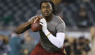 FILE - In this Dec. 26, 2015, file photo, Washington Redskins' Robert Griffin III warms up before an NFL football game against the Philadelphia Eagles, in Philadelphia. Cleveland's never-ending search for a franchise quarterback could come down to a competition between RG3 and one of the two rookies this summer. (AP Photo/Matt Rourke, File)