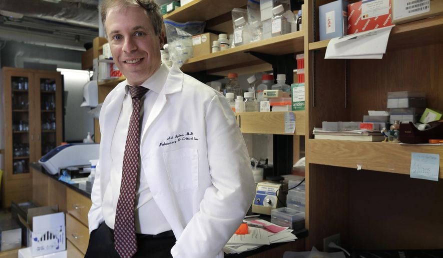 In this Thursday, March 17, 2016, photo, Boston University professor Avi Spira, a medical researcher in chronic obstructive pulmonary disease, stands for a portrait in his lab at Boston University School of Medicine, in Boston. Johnson & Johnson's ambitious project to find ways to prevent diseases or stop them early on has been expanding rapidly and now includes about two dozen collaborations with outside research partners. One just being announced involves Boston University researchers. (AP Photo/Steven Senne)