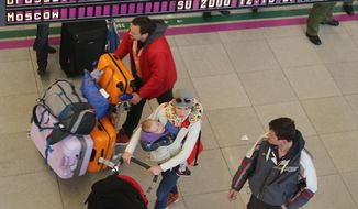 Passengers at Warsaw's Frederic Chopin airport in Warsaw, Poland on Tuesday, March 22, 2016,  pass by an information board that lists flights to Brussels as canceled, following deadly blasts at Bussels' airport.  (AP Photo/Czarek Sokolowski)