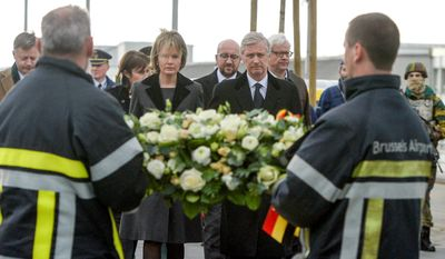 Belgium's King Philippe and Queen Mathilde lay a wreath with firefighters in front of the damaged terminal at the Brussels Airport on Wednesday.