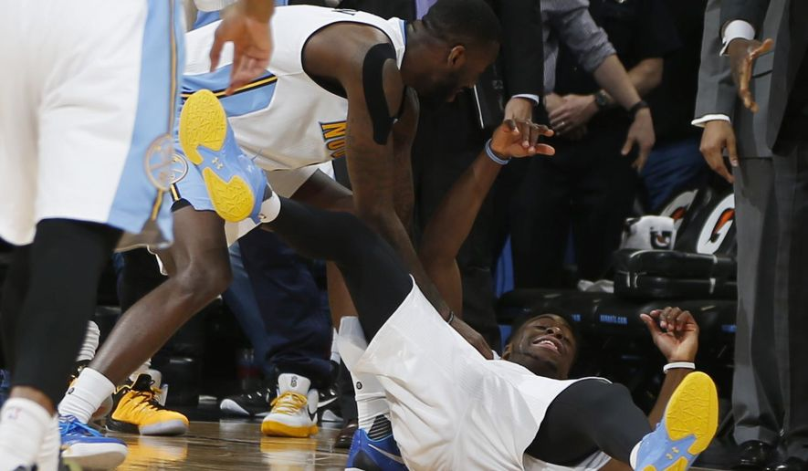 Denver Nuggets guard JaKarr Sampson, left, congratulates guard Emmanuel Mudiay after he hit a three-point shot with time expiring in the second half of an NBA basketball game against the Philadelphia 76ers Wednesday, March 23, 2016, in Denver. The Nuggets won 104-103 on Mudiay's three-point shot as time ran out in the half. (AP Photo/David Zalubowski)