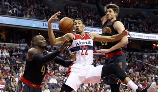 Washington Wizards forward Otto Porter Jr. (22) works to get the rebound between Atlanta Hawks forward Paul Millsap (4) and guard Kyle Korver (26) during the first half of an NBA basketball game Wednesday, March 23, 2016, in Washington. (AP Photo/Alex Brandon)