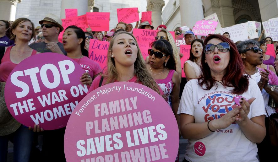 "Planned Parenthood supporters rally for women's access to reproductive health care on ""National Pink Out Day'' at Los Angeles City Hall on Sept. 9, 2015. (Associated Press)"