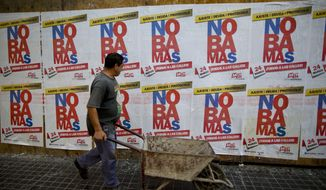 "A man passes in front of banners reading in Spanish ""No more"" in protest against the visit of United States President Barack Obama in Buenos Aires, Argentina, Wednesday, March 23, 2016. Obama is on a two-day visit to Argentina and will meet Wednesday with Argentine President Mauricio Macri. (AP Photo/Ivan Fernandez)"