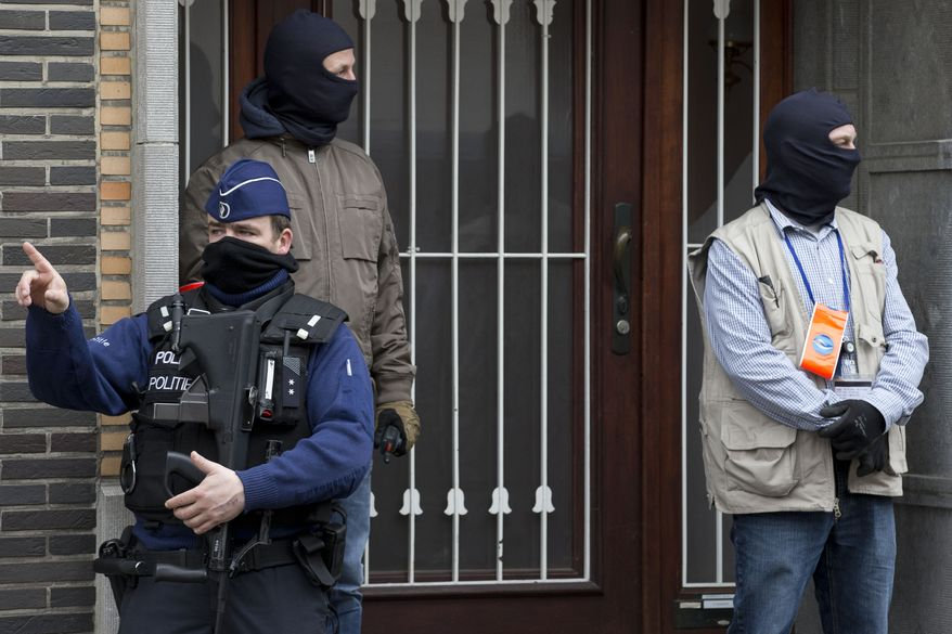 Belgium police stand guard during an investigation in a house in the Anderlecht neighborhood in Brussels, Belgium, Wednesday, March 23, 2016, one day after Tuesday's deadly suicide attacks on the Brussels airport and its subway system. (AP Photo/Peter Dejong)