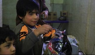 Islamic State militants give candy to boys in Syria in celebration of the terrorist attacks in Brussels. (Image: the Daily Mail)
