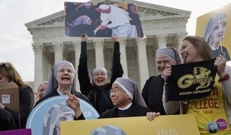 Nuns with the Little Sisters of The Poor, including Sister Celestine, left, and Sister Jeanne Veronique, center, rally outside the Supreme Court in Washington, Wednesday, March 23, 2016, as the court hears arguments to allow birth control in health care plans in the Zubik vs. Burwell case. (AP Photo/Jacquelyn Martin) ** FILE **
