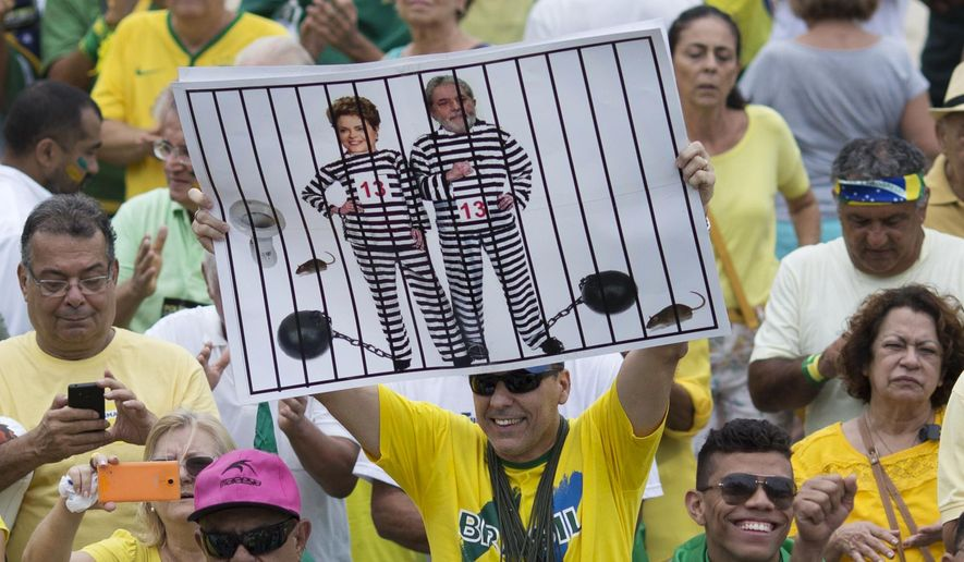 "FILE - In this March 13, 2016 file photo, a demonstrator holds a poster with the photo of Brazilian president Dilma Rousseff and former President Luiz Inacio Lula da Silva in prison stripes during a protest on Copacabana beach in Rio de Janeiro, Brazil. It was the best of times in 2009 when Rio was awarded the games, championed by then-President Luiz Inacio Lula da Silva. He called it a ""sacred day"" and praised the ""strength of Brazil's economy,"" which shrank by 4 percent in 2015 with no improvement in sight. (AP Photo/Silvia Izquierdo, File)"