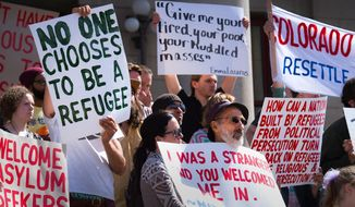 Peter Sprunger-Froese, with hat, joins a group of about 120 people as they stand on the front steps of the Colorado Springs City Hall, Colo., Tuesday, March 22, 2016, to protest against a resolution drafted by Councilman Andres Pico to ban refugees from Syria and other Middle Eastern countries from relocating to Colorado Springs. Pico said his intention was to heighten security, not to disparage refugees, The Gazette reports. (Christian Murdock/The Gazette via AP) ** FILE **