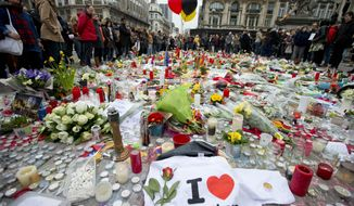 Three balloons in the colors of the Belgian flag fly as people mourn for the victims of the bombings at the Place de la Bourse in the center of Brussels, Belgium, Thursday, March 24, 2016. The Islamic State group has trained at least 400 fighters to target Europe in deadly waves of attacks, deploying interlocking terror cells like the ones that struck Brussels and Paris with orders to choose the time, place and method for maximum carnage. (AP Photo/Peter Dejong)