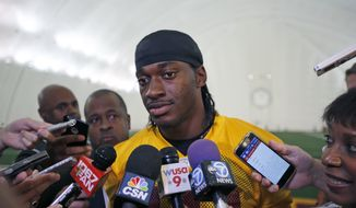 FILE - In this Aug. 18, 2015, file photo, Washington Redskins quarterback Robert Griffin III speaks to reporters after NFL football practice, in Ashburn, Va. The Browns have signed free agent quarterback Robert Griffin III, who hasn't been the same since his dazzling rookie season in Washington.  Griffin, who didn't play a snap in 2015, was recently released by the Redskins.  (AP Photo/Alex Brandon, File)