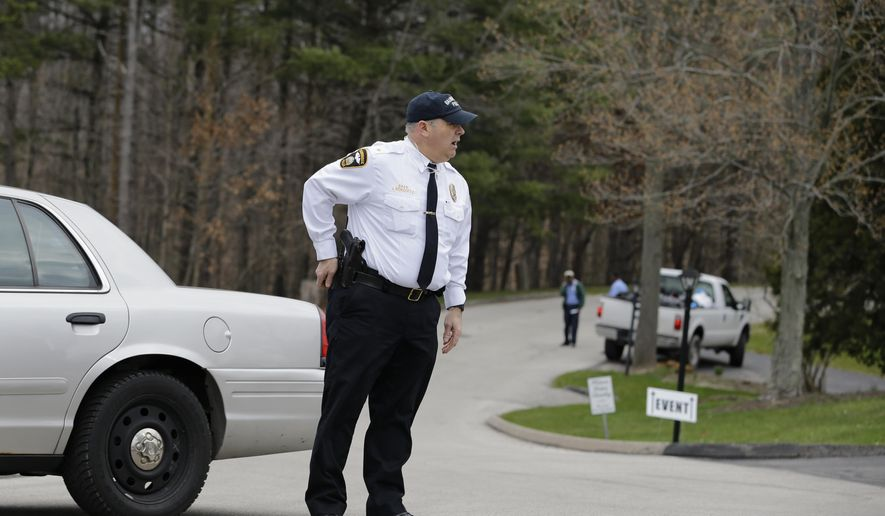 A Bainbridge police officer stands guard down the street from where a shooting occurred at the Hamlet Hills Village, Thursday, March 24, 2016, in Chagrin Falls, Ohio. Police say the shooting happened early Thursday morning in the upscale community 20 miles from Cleveland.  (AP Photo/Tony Dejak)