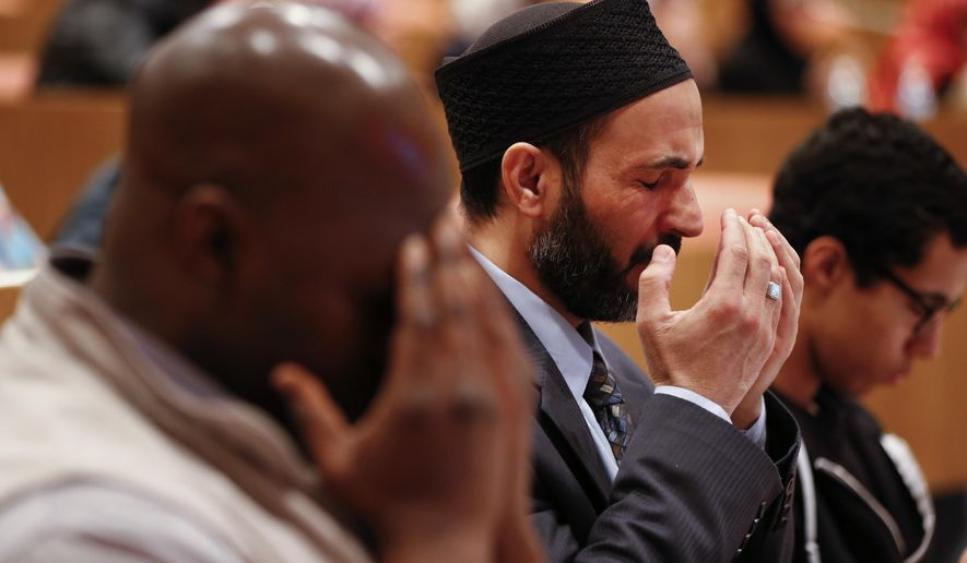 Mohammed Fytahi, of Indianapolis, right, prays Wednesday, March 23, 2016, during a moment of silence as a tribute following the attacks in Brussels on Tuesday, at a Ahmadiyya Muslim Community of Metro Detroit symposium in Dearborn, Mich. (AP Photo/Paul Sancya)