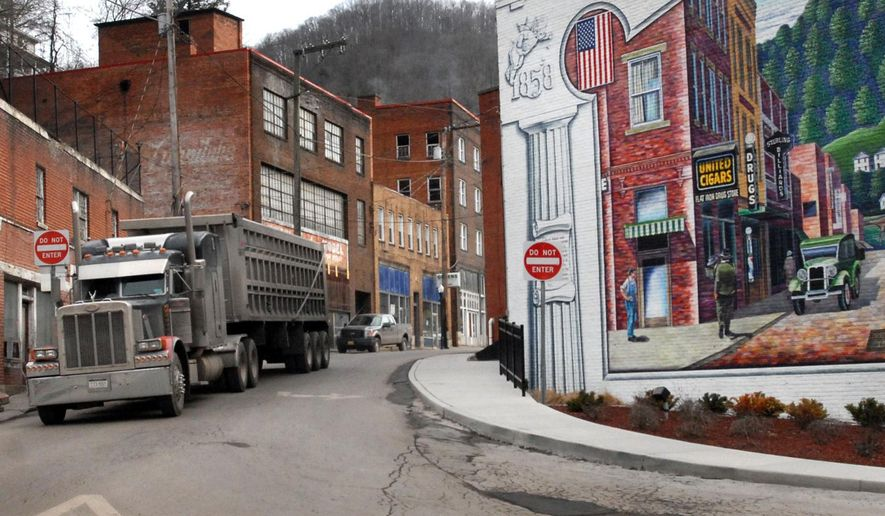 FILE - In a Feb. 9, 2011 file photo, a coal truck drives out of downtown Welch, W.Va. A ccording to U.S. Census figures released Thursday, March 24, 2016, Appalachian coal-producing counties saw steep population declines last year amid a storm of layoffs in the mining industry. McDowell County lost 2.2 percent of its residents to fall below 20,000 population for the first time since the 1900 census.(AP Photo/Jon C. Hancock, File)