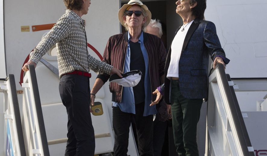 Keith Richards stands between Mick Jagger, left, and Ron Wood as The Rolling Stones deplane at Jose Marti international airport in Havana, Cuba, Thursday, March 24, 2016. The Stones are performing a free concert in Havana on Friday, becoming the most famous act to play Cuba since its 1959 revolution. (AP Photo/Ramon Espinosa)