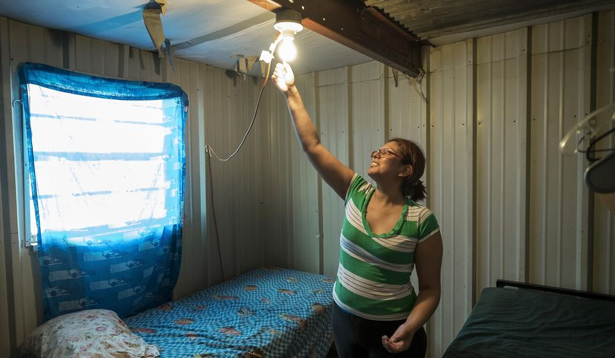 Nora Castillo, 31, reaches up to unscrew a light bulb to turn it off in the two bedroom living space she and her family share in O'Donnell, Texas, on Aug.19, 2015. Throughout the Panhandle and West Texas, motels often serve as housing of last resort for farmworkers.  (Rodolfo Gonzalez/Austin American-Statesman via AP)  AUSTIN CHRONICLE OUT, COMMUNITY IMPACT OUT, INTERNET AND TV MUST CREDIT PHOTOGRAPHER AND STATESMAN.COM, MAGS OUT; MANDATORY CREDIT
