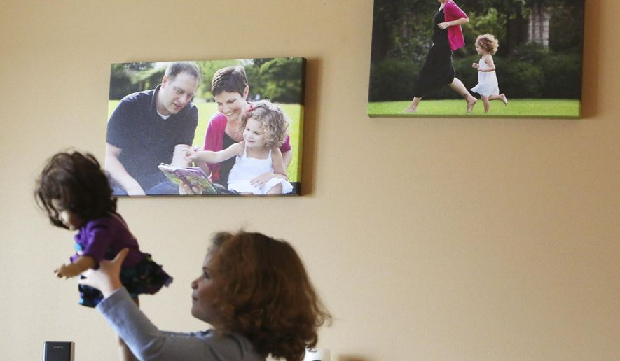 """ADVANCE FOR MONDAY, MARCH 28, 2016 AND THEREAFTER - In a Feb. 24, 2016 photo, Brianna McManamy, 4, plays with her doll, Sweetie, in the living room where photos of her, with her mother Heather and father Jeff, hang on the wall in the background at their home in McFarland, Wis. Heather McManamy passed away last December after a long battle with breast cancer. After a terminal cancer diagnosis, Heather McManamy wrote a collection called """"Cards for Brianna,"""" which will be published in April, that consists of cards and letters for each of the milestones Brianna will pass in her life. (Amber Arnold/Wisconsin State Journal via AP))"""