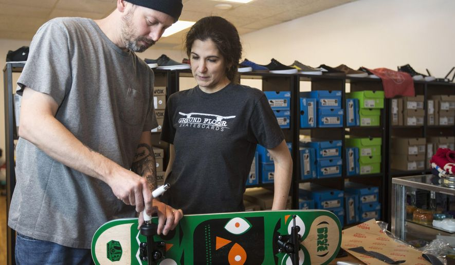 ADVANCE FOR USE SATURDAY, MARCH 26 AND THEREAFTER - In this March 5, 2016 photo, Eric and Alicia Neubauer assemble a skateboard at their independent skateboard shop, Ground Floor Skateboards, in downtown Rockford Ill. (Sunny Strader/Rockford Register Star via AP) MANDATORY CREDIT