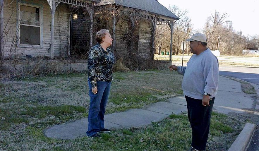 ADVANCE FOR USE SUNDAY, MARCH 27 AND THEREAFTER - In this March 5, 2016 photo, Mounds, Ill., Mayor Rita Flummer stops and chats with a fellow Mounds city council member Raymond Howard outside an abandoned home. The city of Mounds has fallen on hard times. A third of its residential and commercial properties are vacant, dilapidated or abandoned. The city is aware of this problem, Flummer said, and is beginning to address it by starting to enforce city codes. (Stephanie Esters/The Southern Illinoisan via AP) MANDATORY CREDIT