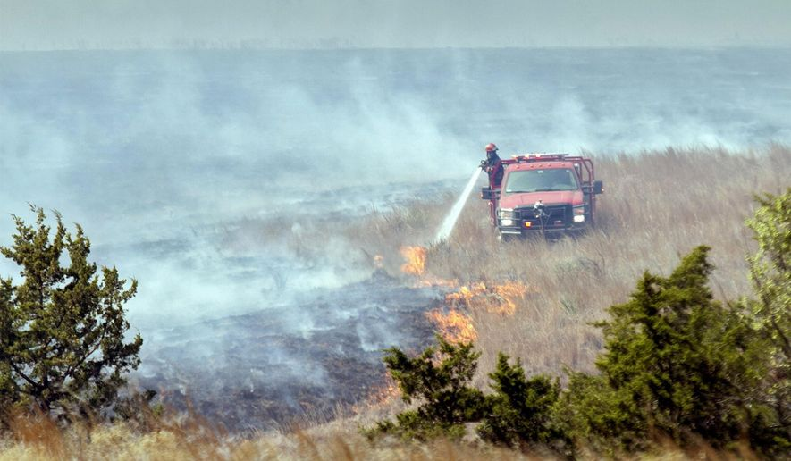 A firefighter crew douses a line of grass fire about 15 miles southwest of Medicine Lodge, Kansas Thursday, March 24, 2016. More than 200 firefighters are battling an active fire line stretching 30 to 40 miles long in Barber County on Thursday.  (Mike Hutmacher/The Wichita Eagle via AP) LOCAL TELEVISION OUT; MAGS OUT; LOCAL RADIO OUT; LOCAL INTERNET OUT; MANDATORY CREDIT