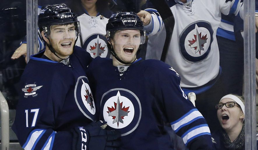 Winnipeg Jets' Adam Lowry (17) and Jacob Trouba (8) celebrate Lowry's goal against the Los Angeles Kings during the second period of an NHL hockey game Thursday, March 24, 2016,  in Winnipeg, Manitoba. (John Woods/The Canadian Press via AP)