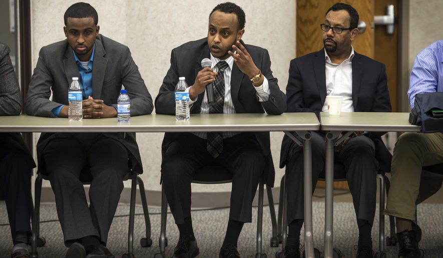 Aman Obsiye, center, speaks about the new phase of civil rights for people of color, immigrants and Muslims and how Somali people fall into all those categories at the Hennepin County Safety Center on Thursday, March 24, 2016, in Minneapolis, Minn.   Federal, state and local law enforcement leaders met with local imams and Muslim community leaders in light of this week's attacks in Brussels and heightened security. (Renee Jones Schneider/Star Tribune via AP)
