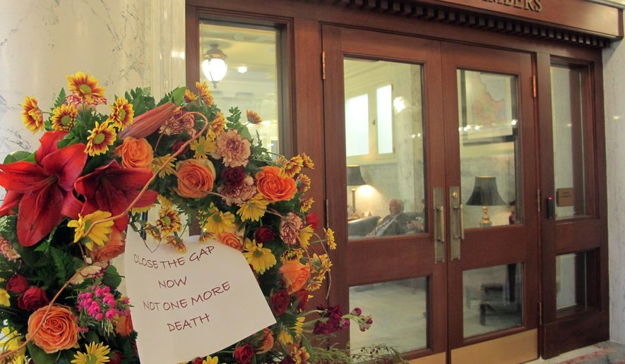 A floral funeral wreath is seen Thursday, March 24, 2016, outside the Idaho Senate chambers in Boise, Idaho. Protesters placed wreaths by the Senate and House chambers to protest lawmakers not passing a Medicaid expansion bill. (AP Photo/Kimberlee Kruesi)