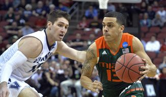 Miami guard Angel Rodriguez (13) drives around Villanova guard Ryan Arcidiacono (15) during the first half of an NCAA college basketball game in the regional semifinals of the men's NCAA Tournament in Louisville, Ky., Thursday, March 24, 2016. (AP Photo/Timothy D. Easley)