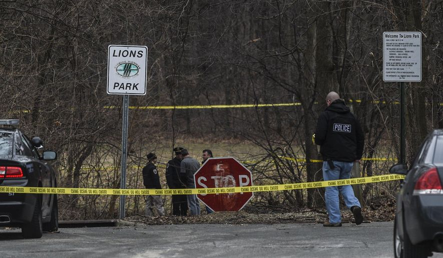 In this March 19, 2016, photo, authorities investigate the scene at Lions Park where Wyoming police found a body in Wyoming, Mich. A 16-year-old boy has been found dead in a park in the Grand Rapids area, the victim of an apparent homicide. (Taylor Ballek/The Grand Rapids Press via AP) ALL LOCAL TELEVISION OUT; LOCAL TELEVISION INTERNET OUT; MANDATORY CREDIT