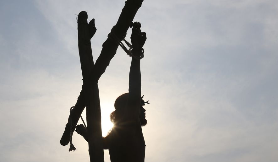 An unidentified Indian actor dressed as Jesus Christ reenacts the crucifixion during Good Friday in Hyderabad, India, Friday, March 25, 2016. Christians are marking the solemn period of Easter. (AP Photo/Mahesh Kumar A.)