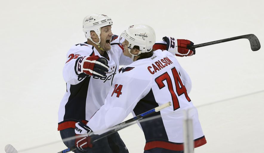 Washington Capitals defenseman John Carlson (74) celebrates his winning goal in overtime with teammate Jason Chimera (25) during an NHL hockey game against the New Jersey Devils, Friday, March 25, 2016, in Newark, N.J.  (AP Photo/Mel Evans)